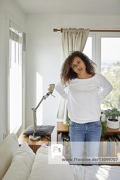 Bildnis einer Frau mit Händen auf der Hüfte im Schlafzimmer stehend