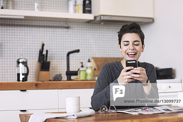 Happy woman using mobile phone at dining table in kitchen