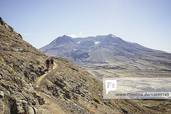 Rückansicht von Freunden  die am sonnigen Tag auf dem Berg gegen den Himmel wandern