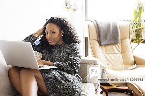 Lächelnde Frau benutzt Laptop-Computer,  während sie auf dem Sofa sitzt