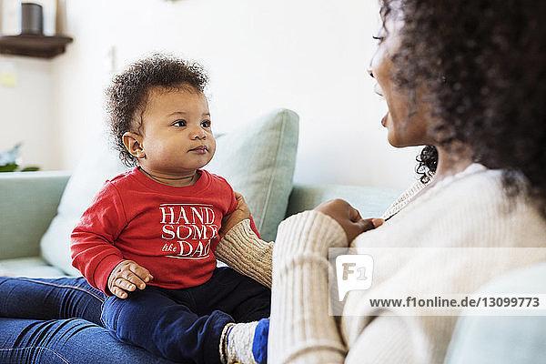 Säugling schaut die Mutter an  während er zu Hause auf ihrem Schoß sitzt
