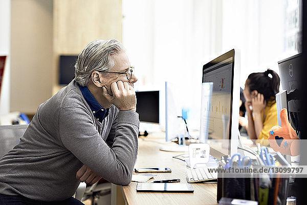 Geschäftsmann schaut auf Desktop-Computer mit einer Kollegin im Hintergrund