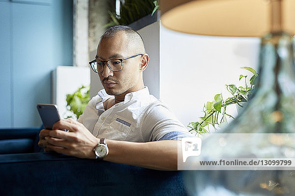 Businessman using mobile phone while sitting on sofa in creative office
