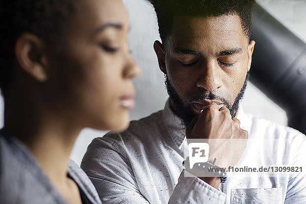 Thoughtful young man with eyes closed by woman at home