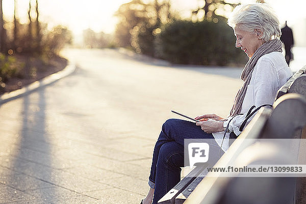 Senior woman using tablet computer while sitting on bench at footpath