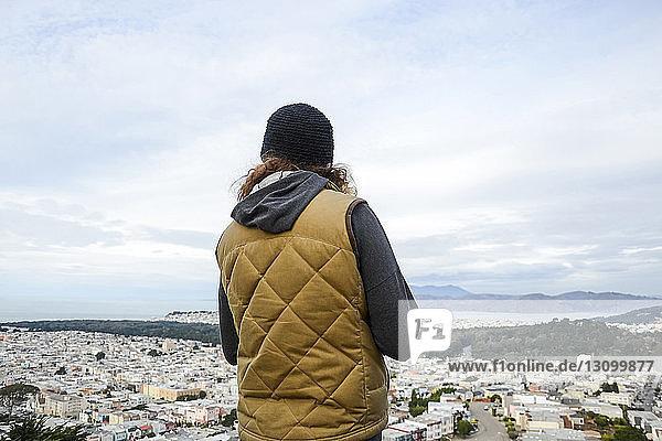 Rückansicht einer Frau  die das Stadtbild vor bewölktem Himmel betrachtet