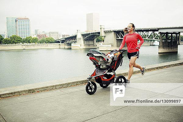 Frau joggt mit Kinderwagen auf Fußweg am Fluss gegen Brücke