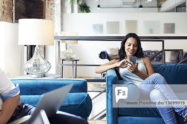 Smiling businesswoman using mobile phone while sitting on sofa at creative office