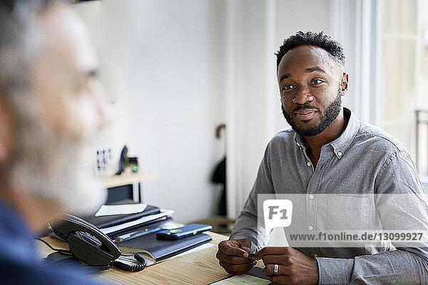 Zuversichtlicher Geschäftsmann schaut auf männlichen Amtskollegen
