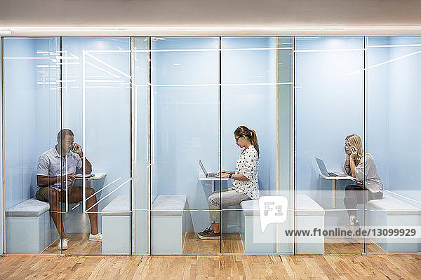 Multi-ethnic business people using laptops while sitting in cubicles at office