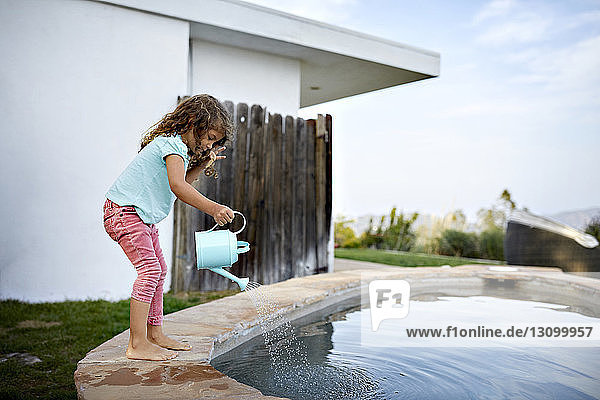 Side view of girl pouring water in swimming pool against sky