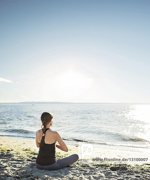 Rear view of woman meditating at beach against sky during sunny day