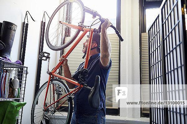 Geschäftsmann  der ein Fahrrad trägt  während er im Kreativbüro einen Fahrradträger betrachtet