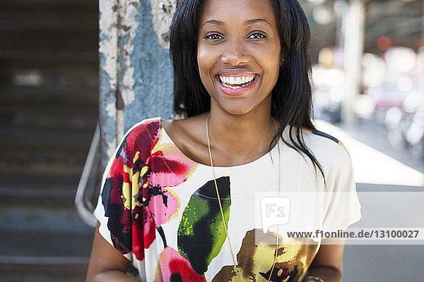 Portrait of happy woman standing on sidewalk