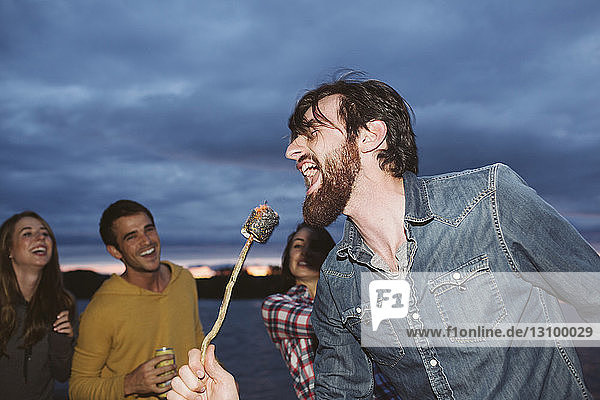 Smiling friends looking at man singing while holding roasted marshmallow on stick against cloudy sky