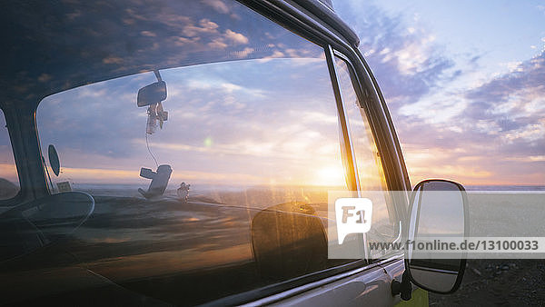 Motor home at beach against cloudy sky during sunset