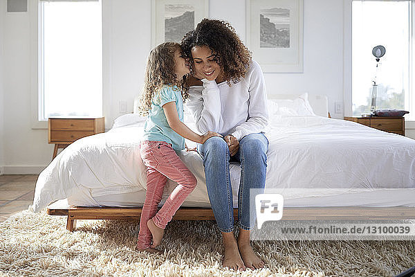 Daughter whispering to mother sitting on bed at home