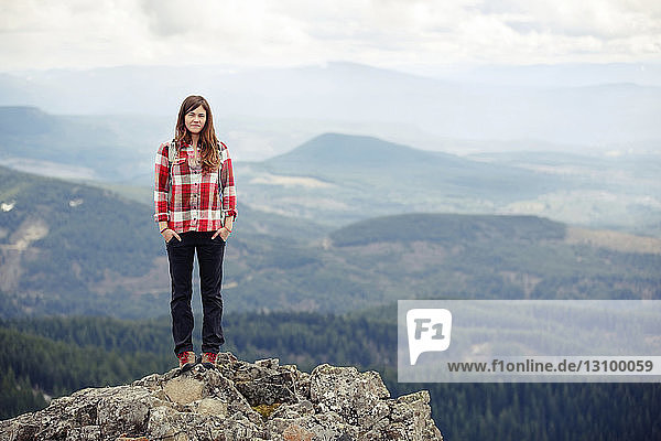 Portrait of smiling woman standing on top of mountain against cloudy sky