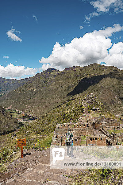 Rear view of hiker looking at old ruins while standing on mountain against sky at Pisac