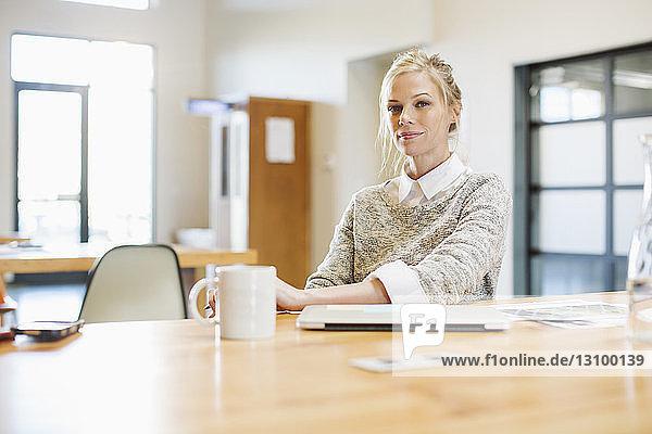 Porträt einer selbstbewussten Geschäftsfrau am Tisch sitzend mit Laptop-Computer im Büro
