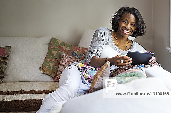 Portrait of happy woman holding tablet computer while relaxing on sofa at home