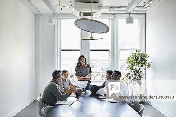 Geschäftsmann bespricht Dokumente mit Kollegen im Konferenzraum des Kreativbüros