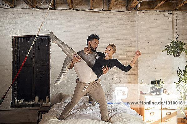 Junger Mann trägt fröhliche Frau zu Hause im Bett