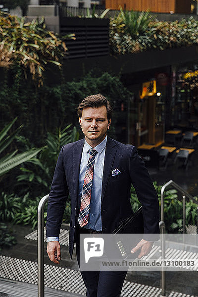 Portrait of confident well-dressed businessman in city