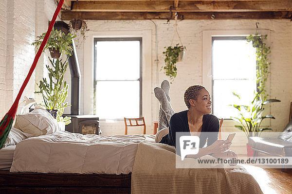 Glückliche Frau schaut weg  während sie ein Smartphone im Schlafzimmer hält