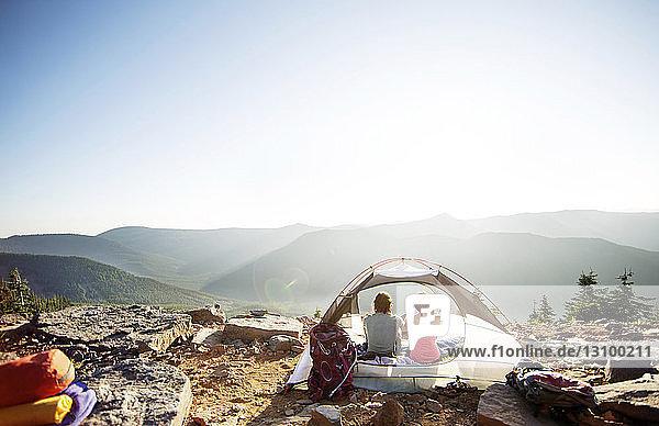 Rückansicht eines Paares  das sich im Zelt auf dem Berg entspannt