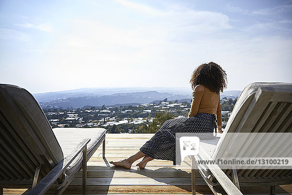 Rear view of woman looking at view while sitting on deckchair against sky
