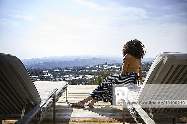 Rückansicht einer Frau  die im Liegestuhl sitzend gegen den Himmel blickt