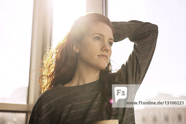 Thoughtful woman looking away while standing by window at home