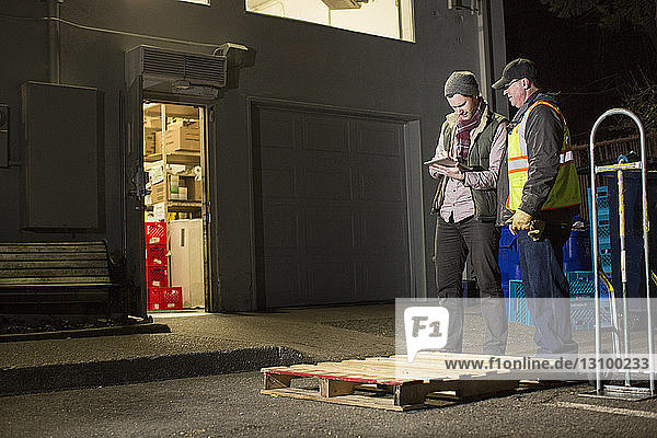 Workers using tablet computer while standing by warehouse at night