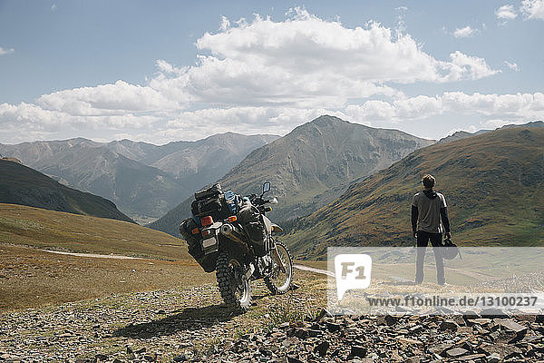 Rear view of biker standing by motorbike on mountain against cloudy sky