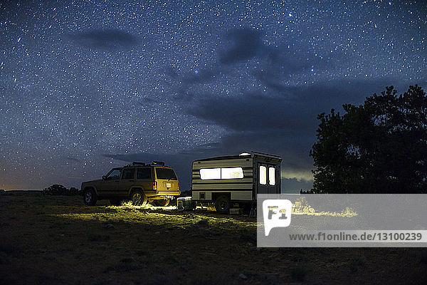 Auto und beleuchteter Reiseanhänger gegen Sternenfeld