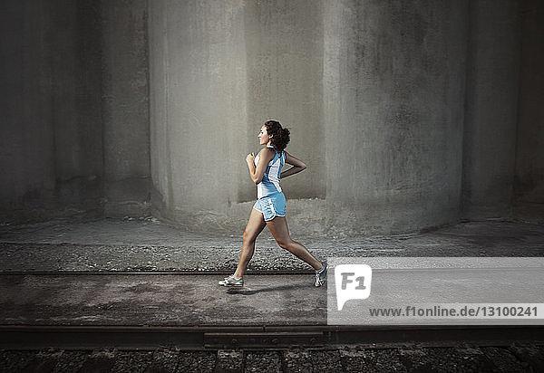 Entschlossene Sportlerin joggt auf einem Fußweg an einer Eisenbahnschiene