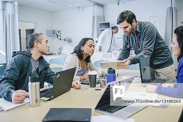 Männlicher Arzt diskutiert mit Kollegen über Tablet-Computer im Behandlungszimmer