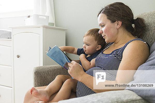 Mutter mit Sohn liest zu Hause Buch auf Stuhl