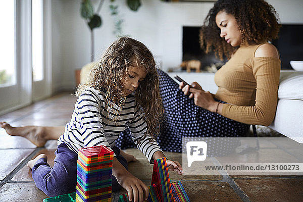 Mutter benutzt Mobiltelefon  während die sitzende Tochter im Wohnzimmer mit Spielzeug spielt