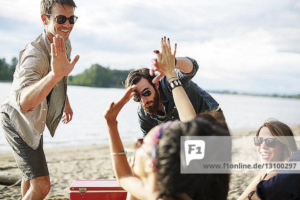 Glückliche Freunde beim Abklatschen  während sie am Flussufer bei bewölktem Himmel genießen