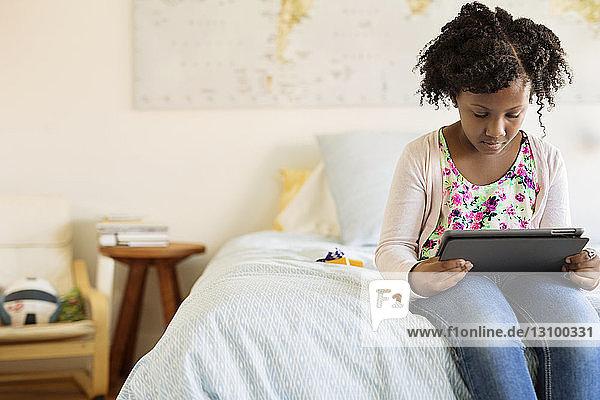 Mädchen benutzt Tablet-Computer  während sie auf dem Bett sitzt