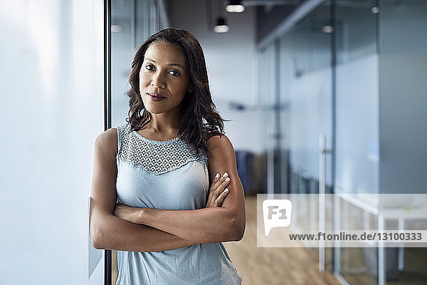 Portrait of confident smiling businesswoman standing with arms crossed by glass wall in office corridor