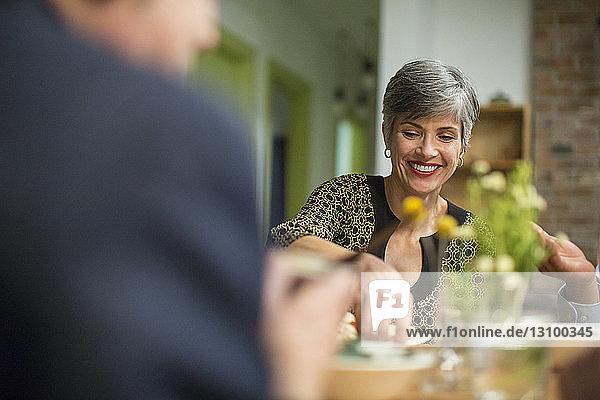 Lächelnde Frau bei Tisch während des geselligen Beisammenseins