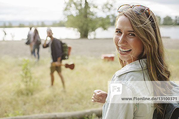 Portrait of happy woman with backpack on field