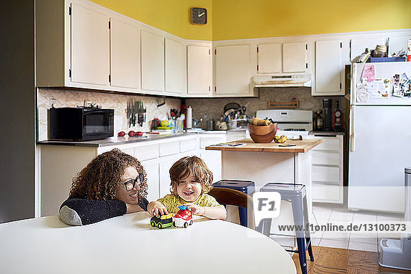 Mother looking at son playing with toys while sitting in kitchen