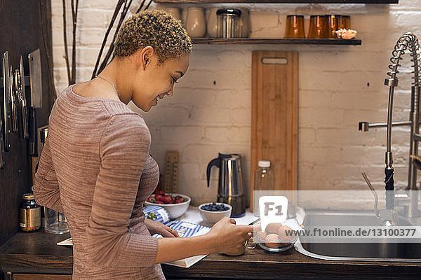 Glückliche Frau benutzt Smartphone in der Küche