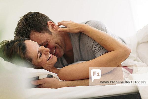 Lächelndes Paar zu Hause im Bett