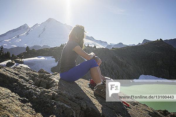 Weibliche Wanderin sitzt bei Sonnenschein auf Berg gegen Himmel