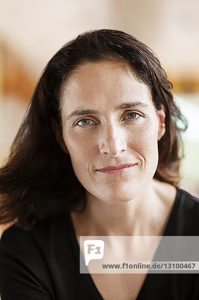 Close-up portrait of smiling woman at home